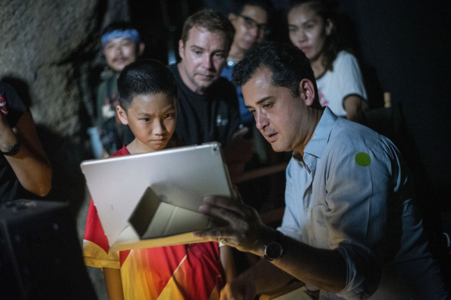 "In this Nov. 14, 2018, photo provided by De Warrenne Pictures, director Tom Waller, right, talks to actors for a scene of his film ""The Cave"" in Thailand. [Photo: AP]"
