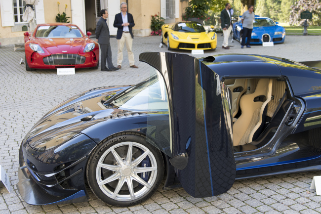People looking at a 2015 Koenigsegg One:1 model car in front of a Aston Martin One-77 Coupe (2011), red, Ferrari LaFerrari (2015), yellow, and a Bugatti Veyron EB 16.4 Coupe (2010), blue, part of some 25 luxury cars owned by Teodoro Obiang, the son of the Equatorial Guinea's President Teodoro Obiang Nguema Mbasogo are pictured before an auction of sales house Bonhams at the Bonmont Abbey Golf & Country Club in Cheserex near Geneva, Switzerland, Sunday, September 29, 2019. [Photo: Laurent Gillieron/Keystone via AP]