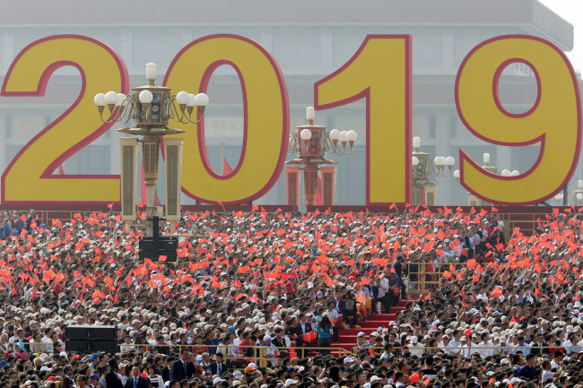 People wave Chinese national flags marking the 70th founding anniversary of People's Republic of China in Beijing on October 1, 2019. [Photo: VCG]