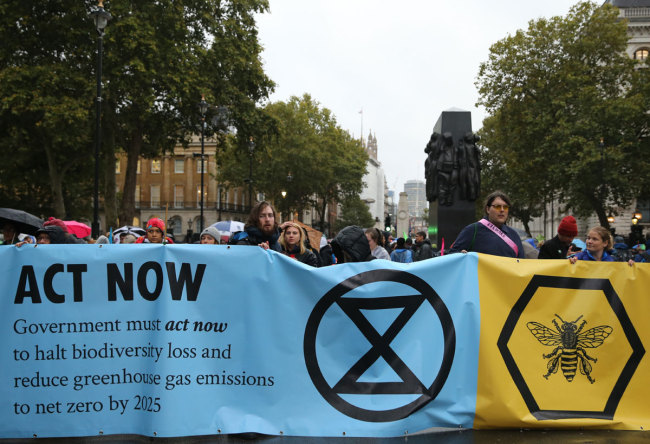 Climate change activists from the Extinction Rebellion block the road with a banner that calls on the government to act now to reduce greenhouse gas emissions to halt biodiversity loss on Whitehall outside Downing Street in central London, on October 7, 2019 during the group's global climate protests. [Photo: AFP]