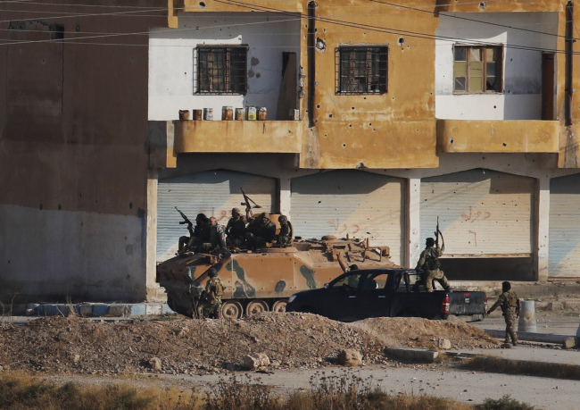 In this photo taken from the Turkish side of the border between Turkey and Syria, in Akcakale, Sanliurfa province, southeastern Turkey, Turkish-backed Syrian opposition fighters advance with theirs armoured personnel carrier in Tel Abyad, Syria, Sunday, Oct. 13, 2019. [Photo: AP/Lefteris Pitarakis]