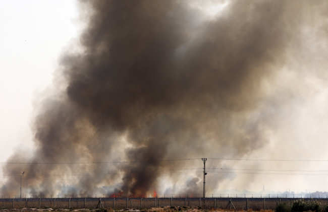 In this photo taken from the Turkish side of the border between Turkey and Syria, in Akcakale, Sanliurfa province, southeastern Turkey, smoke billows from fires on targets in Tel Abyad, Syria, caused by bombardment by Turkish forces, Sunday, Oct. 13, 2019. [Photo: AP/Lefteris Pitarakis]