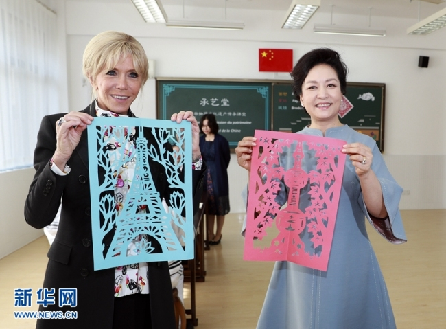 Peng Liyuan, wife of Chinese President Xi Jinping and Brigitte Macron, wife of French President Emmanuel Macron visit a local middle school in Shanghai on Tuesday, November 05, 2019. [Photo: Xinhua]