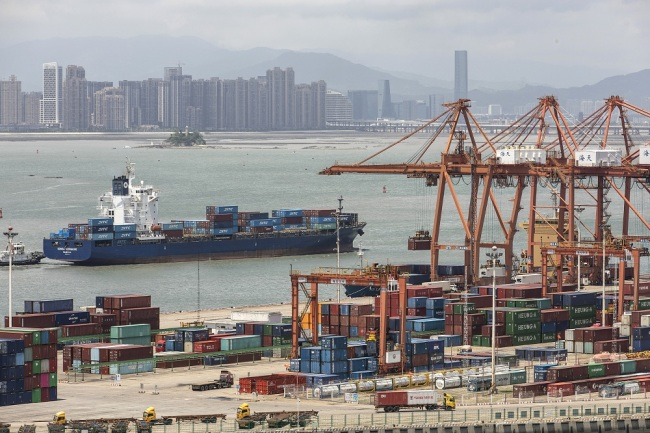 A container ship passes in front of containers and gantry cranes at Haitian Container Terminal, operated by the Xiamen Port Authority, in Xiamen, China, Aug. 26, 2019. [File Photo: VCG]