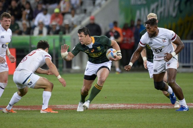 South Africa's Ruhan Nel (C) runs with the ball during the Cape Town leg of the World Rugby Sevens Series rugby match between South Africa and USA on December 14, 2019 at the Cape Town Stadium in Cape Town. [Photo: AFP/ RODGER BOSCH]