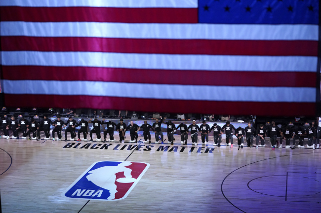 Members of the Orlando Magic and Brooklyn Nets kneel around a Black Lives Matter logo during the national anthem before the start of an NBA basketball game Friday, July 31, 2020, in Lake Buena Vista, Fla. [Photo: AP]